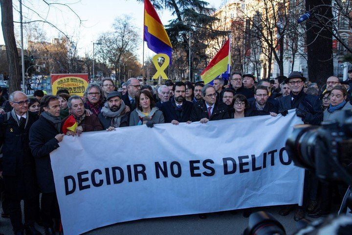 """El entonces presidente de la Generalitat, Quim Torra tras una pancarta con el lema """"Decidir no es un crimen"""", en 2019. Foto: EFE"""