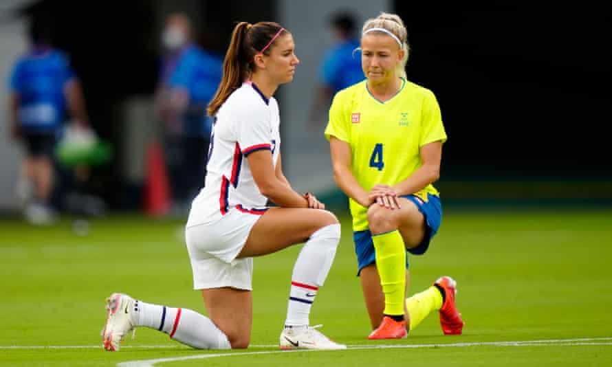 El estadounidense Alex Morgan y la sueca Hanna Glas se arrodillan antes de su partido de fútbol en el estadio de Tokio.