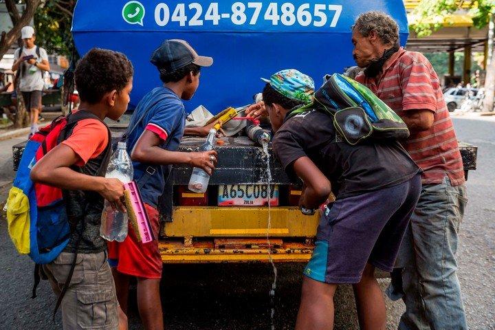 Niños y adolescentes beben agua de un camión cisterna en una calle de Caracas, hace días, durante un receso en su tarea de limpieza de cristales.  Foto: EFE