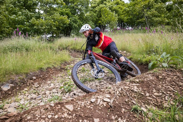 Male cyclist in red riding the Vitus Escarpe 29 CRS trail mountain bike through woodland