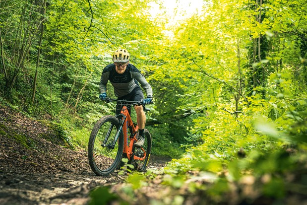 Male cyclist riding the Santa Cruz Blur XC X01 AXS RSV full suspension mountain bike through woodland