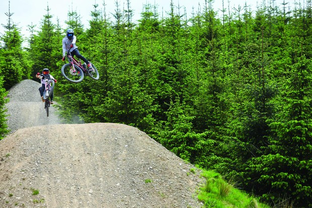 Two cyclists riding downhill bikes on jumps